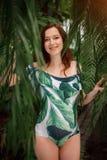 Femme rousse caucasienne enceinte de sourire dans le maillot de bain dans la prairie de paume Photo libre de droits