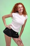 Femme rousse dans de petits shorts, d'isolement sur le vert photo libre de droits