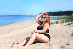 Femme rousse dans des lunettes de soleil se reposant sur la plage Images stock