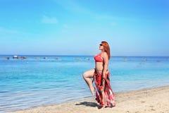 Femme rousse dans des lunettes de soleil se reposant sur la plage Photos stock