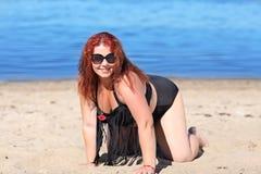 Femme rousse dans des lunettes de soleil se reposant sur la plage Image libre de droits