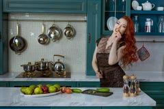 Femme rousse dans la cuisine Photos libres de droits