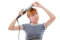 Femme rousse dans le T-shirt rayé utilisant le fer de bordage d'isolement sur le fond blanc Photographie stock