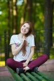 Femme rousse de sourire de jeunes belle dans la chemise rouge d'espadrilles de jeans se reposant sur le banc touchant son fond tr Photo stock