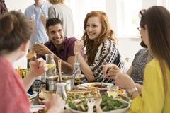 Femme rousse de sourire mangeant le dîner Image libre de droits