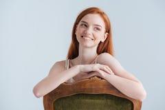 Femme rousse de sourire s'asseyant sur la chaise Photographie stock