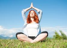 Femme rousse de yoga dans la pose de méditation Photographie stock libre de droits