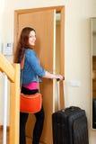 Femme rousse heureuse avec le bagage fermant à clef la porte et partant de elle Photographie stock libre de droits