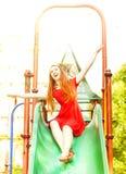 Femme rousse heureuse sur une glissière d'enfants Image stock
