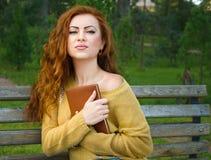 Femme rousse s'asseyant sur un banc avec le livre Photos stock