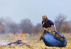 Femme rural aîné brûlant les lames tombées Photos stock