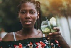 Femme rwandaise avec le verre de coctail dans la barre d'extérieur photo libre de droits