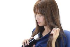 Femme séchant de beaux longs cheveux droits utilisant le dessiccateur photo stock