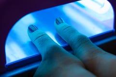 Femme séchant le vernis à ongles le processus de créer un plan rapproché de mains de manucure Soin de clou image stock