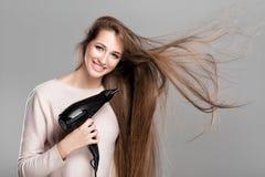 Femme séchant ses cheveux avec le dessiccateur photo stock