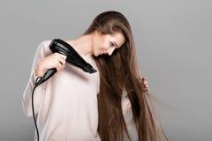 Femme séchant ses cheveux avec le dessiccateur photo libre de droits