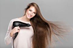 Femme séchant ses cheveux avec le dessiccateur photographie stock libre de droits