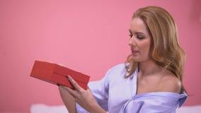 Femme séduisante très heureuse avec le présent précieux dans le boîte-cadeau rouge, jour de valentines clips vidéos