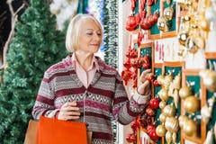 Femme sélectionnant des ornements de Noël au magasin Image libre de droits