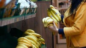 Femme sélectionnant la banane dans le département de produit d'épicerie banque de vidéos