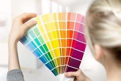 Femme sélectionnant la couleur intérieure à la maison de peinture du catalogue d'échantillon Photographie stock libre de droits