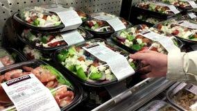 Femme sélectionnant la salade grecque à l'intérieur du magasin de Costco banque de vidéos