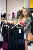 Femme sélectionnant une robe tout en faisant des emplettes pour des vêtements Photos stock