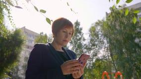Femme sérieuse avec les cheveux rouges utilisant le smartphone dehors avec l'angle faible rétro-éclairé et banque de vidéos