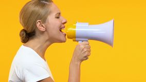 Femme sérieuse criant dans le mégaphone, annonçant l'information, protestation sociale banque de vidéos