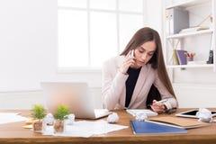 Femme sérieuse d'affaires au travail parlant au téléphone Image stock
