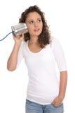 Femme sérieuse d'isolement écoutant au téléphone de boîte en fer blanc des actualités ou le ch Image libre de droits