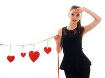 Femme sérieuse de brune dans l'amour posant avec le coeur rouge sur le fond d'isolement sur le fond blanc Photographie stock