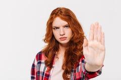 Femme sérieuse de gingembre dans le geste d'arrêt d'apparence de chemise à l'appareil-photo photos stock