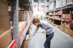 Femme sérieuse de personnel wrting sur le bloc-notes au supermarché Image libre de droits