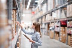 Femme sérieuse de personnel wrting sur le bloc-notes au supermarché images libres de droits