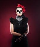 Femme sérieuse en jour du masque mort sur le rouge Image stock
