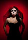 Femme sérieuse en jour du masque mort sur le rouge Photographie stock libre de droits