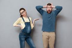 Femme sérieuse enceinte se tenant près de l'homme criard Photos libres de droits