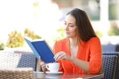 Femme s?rieuse lisant un livre remuant le caf? dans une barre image stock