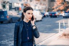 Femme sérieuse parlant sur le mobile dans la ville photographie stock libre de droits