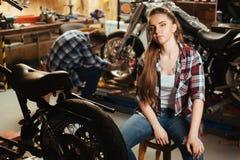 Femme sérieuse s'asseyant dans le garage de son ami Photographie stock