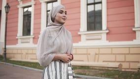 Femme sûre et attirante portant un hijab Inclinaison de marche de jeune femme par la rue de ville avec beau rose et clips vidéos