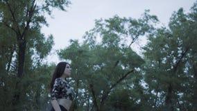 Femme sûre mignonne de portrait exécutant une exposition avec la flamme se tenant dans la forêt ou le parc Artiste habile de fire banque de vidéos