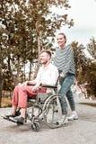 Femme sûre souriant et poussant le fauteuil roulant de son ami handicapé photo libre de droits
