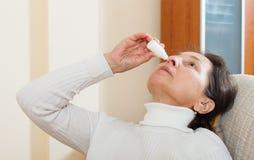 Femme s'égouttant des gouttes pour le nez Photos libres de droits