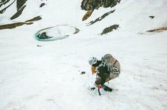 Femme s'élevante avec l'alpinisme de hache de sac à dos et de glace image stock