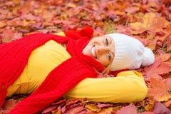Femme s'étendant dans des feuilles rouges Photos stock