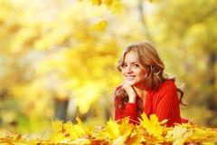 Femme s'étendant sur des feuilles d'automne Images stock