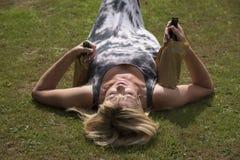 Femme s'étendant sur l'herbe saisissant des bouteilles à bière Image libre de droits