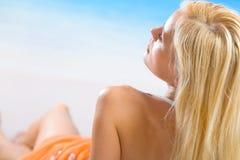 Femme s'étendant sur la plage Photo stock